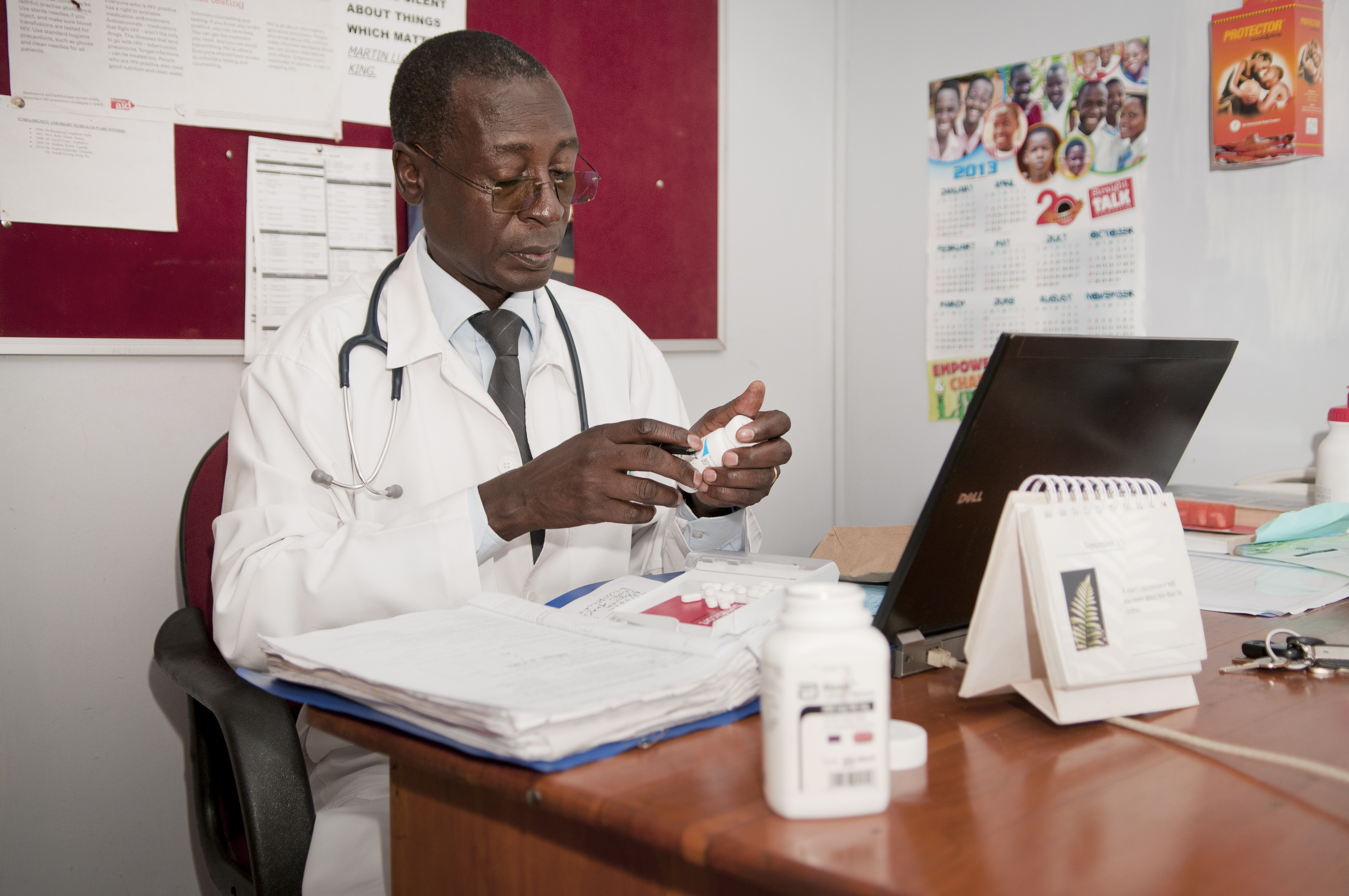 Dr. Stephen Watiti looks at the medicine of his patient Richard Kunya in his office in Mildmay hospital in Lweza, Uganda on April 18 2013.